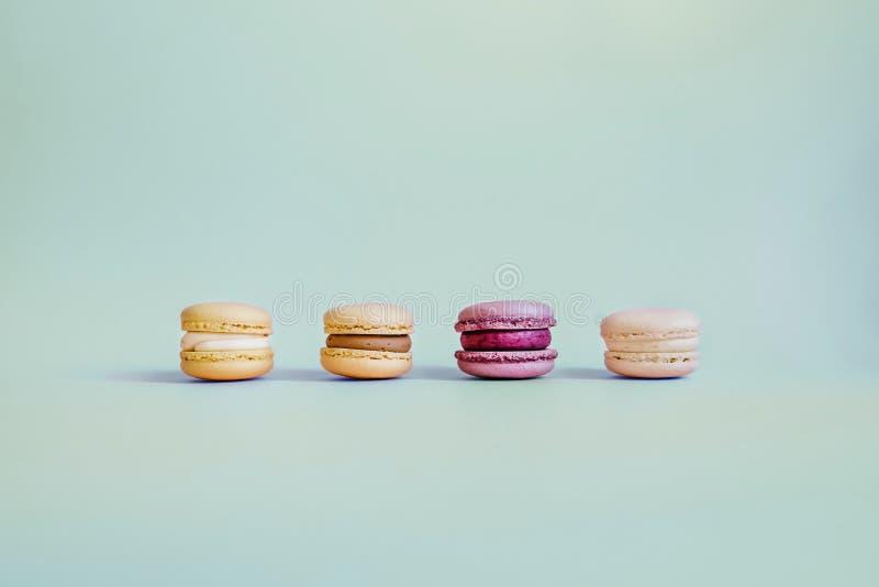 在绿松石背景的四个色的蛋白杏仁饼干 免版税库存图片