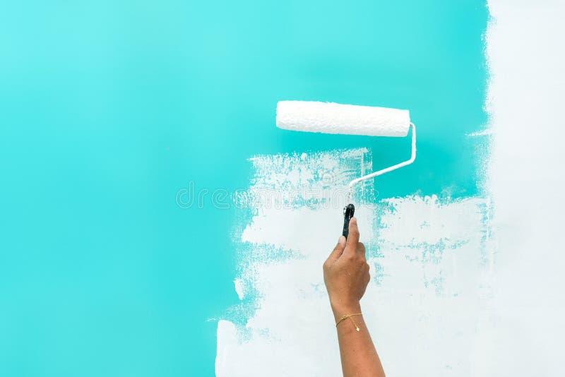 在绿松石色的墙壁的妇女绘画有漆滚筒的 免版税库存图片
