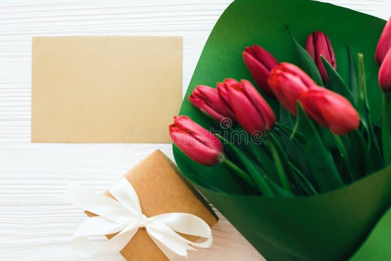 在绿皮书的美丽的红色郁金香花束,礼物盒和工艺卡片与空间文本的在平白色木的背景放置 ?? 库存照片