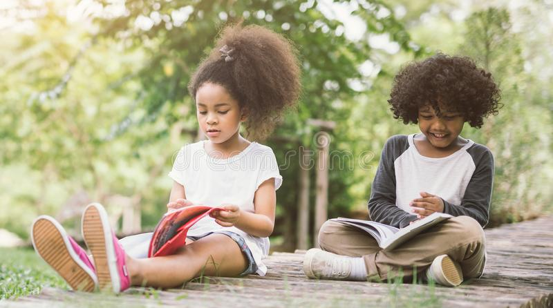 在绿色之间的一点蓬松卷发儿童女孩阅读书钉牢有朋友的草甸庭院 免版税图库摄影