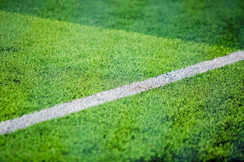 在绿色人为草皮的白色旁边lind背景的 免版税库存图片