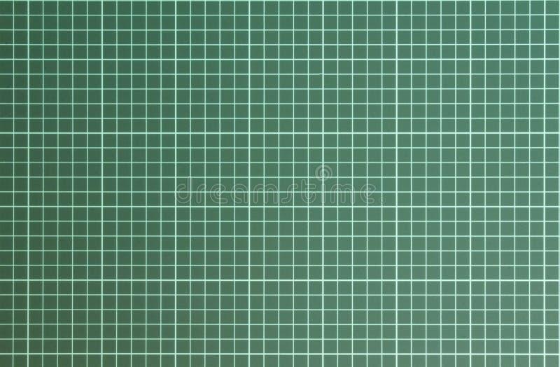在绿色切开的席子背景关闭的白色方格的样式  E 免版税库存图片
