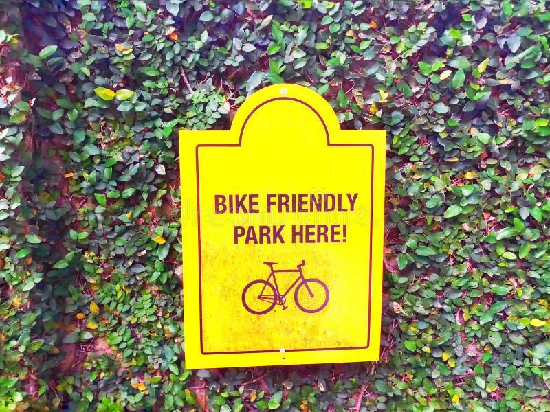 在绿色叶子背景的自行车停放的标志 库存图片