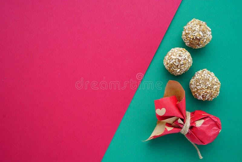 在绿色和桃红色的平的被放置的手工制造椰子圆的糖果上升了与心脏2月14日的玫瑰色背景 免版税库存图片
