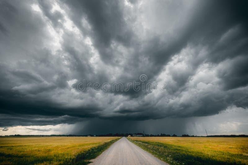 在绿色和黄色领域和风雨如磐的云彩中间铺石渣路在它上 库存照片