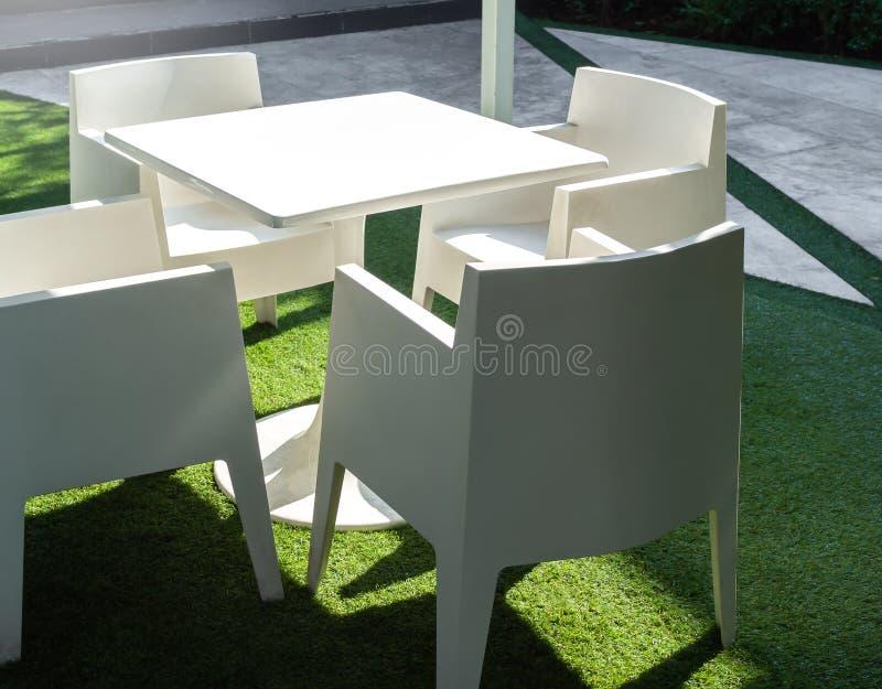 在绿色围场布置的白色现代室外饭桌 图库摄影