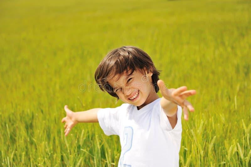 在绿色域的愉快的孩子与广泛 库存图片