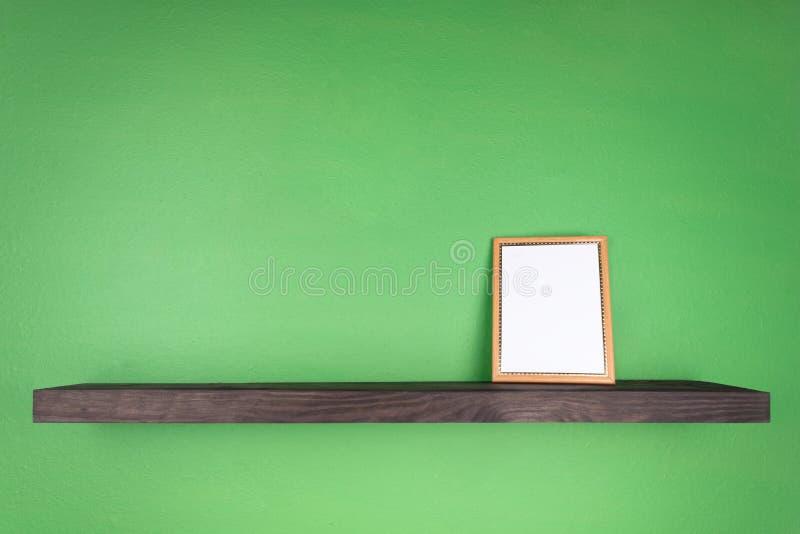 在绿色墙壁上有与相框站立树的纹理的一个黑暗色架子 免版税图库摄影