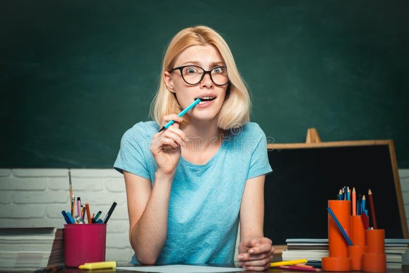 在绿色墙壁黑板背景的微笑的女生或妇女老师画象 老师是熟练的领导 ?? 免版税库存照片
