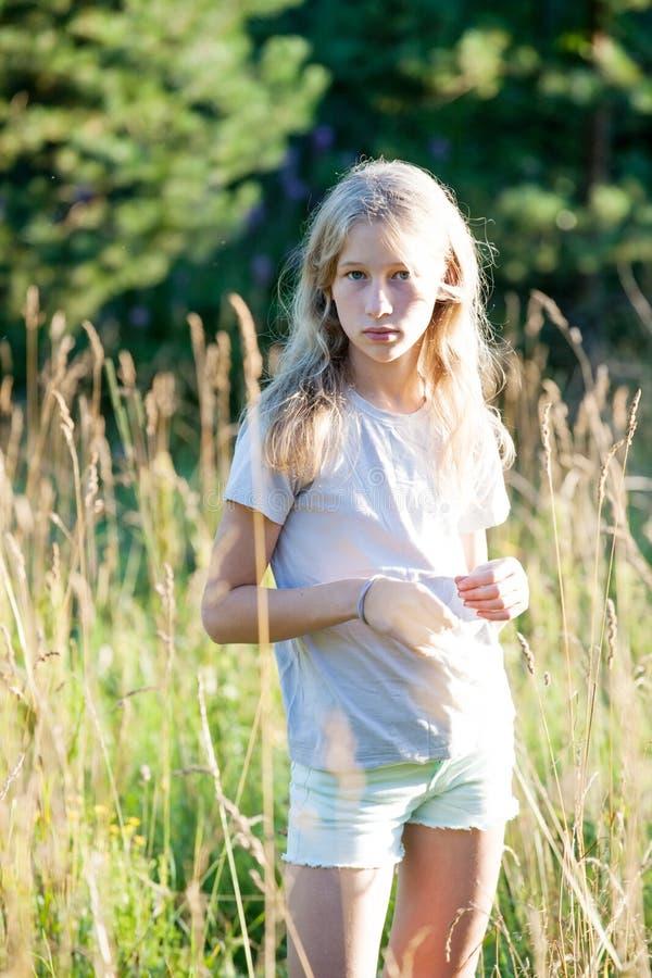 在绿色夏天室外草甸的青少年的白肤金发的白色女孩身分 免版税库存图片