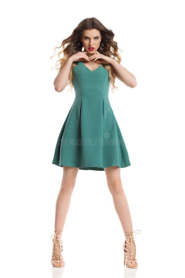 在绿色套衫连超短裙和高跟鞋的时装模特儿分开站立腿 库存图片