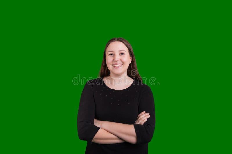 在绿色屏幕上的俏丽的女性横渡的胳膊好的微笑 免版税库存图片