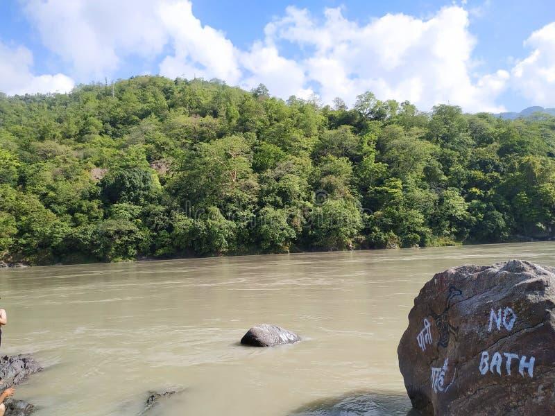 在绿色山前面的美丽的河 库存照片