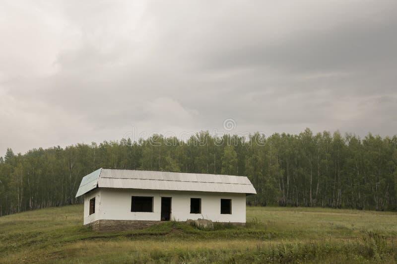 在绿色山的偏僻的白色被忘记的大厦 与很多云彩的深深灰天空 很远森林 横向 库存照片