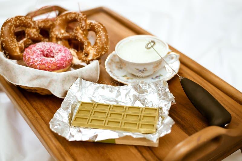 在绿色巧克力用中国matcha茶,古色古香的瓷杯子有打好的奶油的和椒盐脆饼的焦点与被冰的油炸圈饼 免版税库存照片