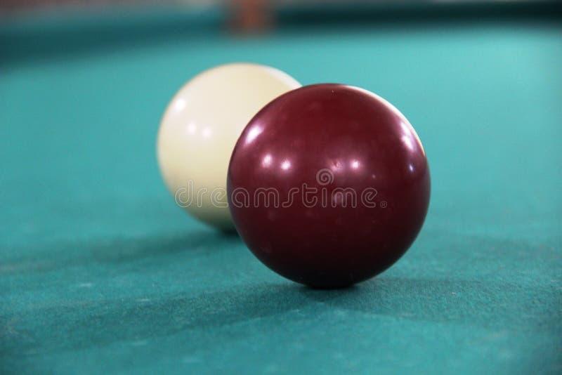 在绿色布料桌、母球和白色球上的两撞球 俄国台球 库存照片