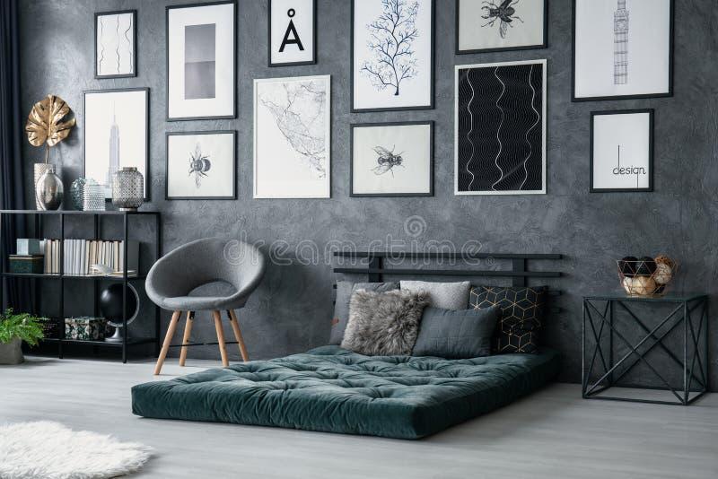 在绿色床垫旁边的灰色扶手椅子在与海报画廊的卧室内部  实际照片 免版税图库摄影