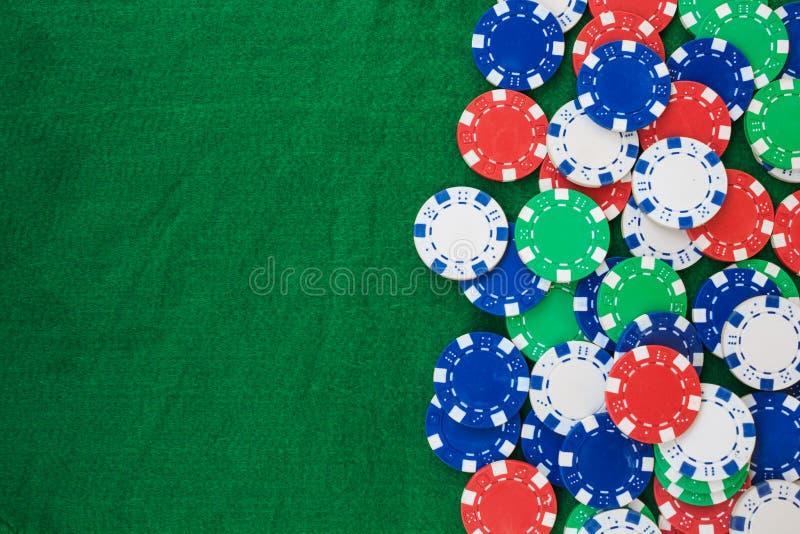 在绿色感觉的背景的五颜六色的赌博的芯片与拷贝空间 免版税库存照片