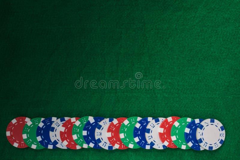 在绿色感觉的背景的五颜六色的赌博的芯片与拷贝空间 免版税库存图片