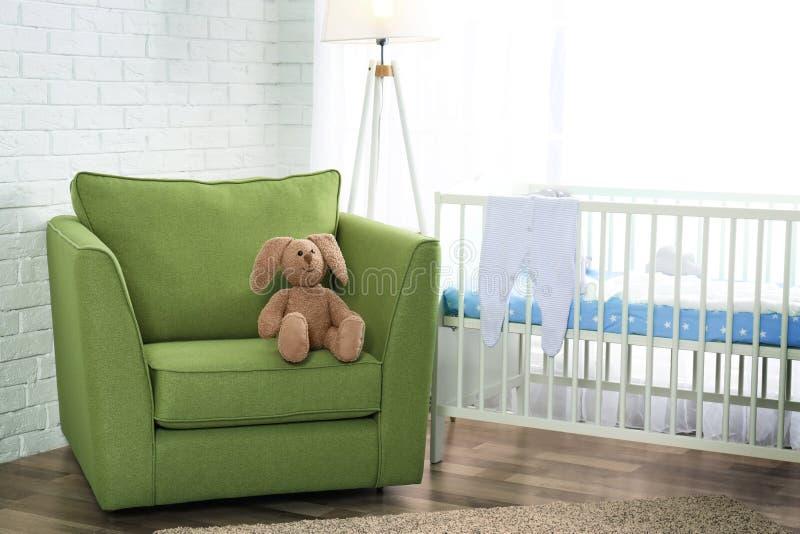 在绿色扶手椅子的逗人喜爱的兔宝宝玩具 库存照片
