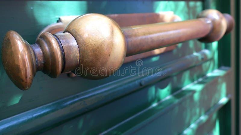 在绿色木门的老黄铜把柄 免版税库存图片