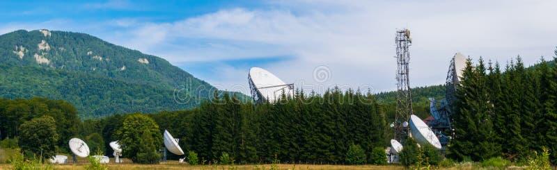 在绿色杉树森林卫星通讯掩藏的大卫星盘天线在Cheia, Prahova,罗马尼亚集中 免版税库存图片