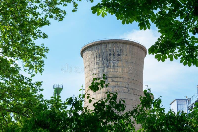 在绿色树植被中掩藏的具体塔能源厂 库存照片
