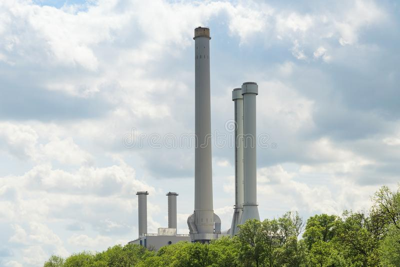 在绿色树的高工业烟囱在森林里 免版税库存照片