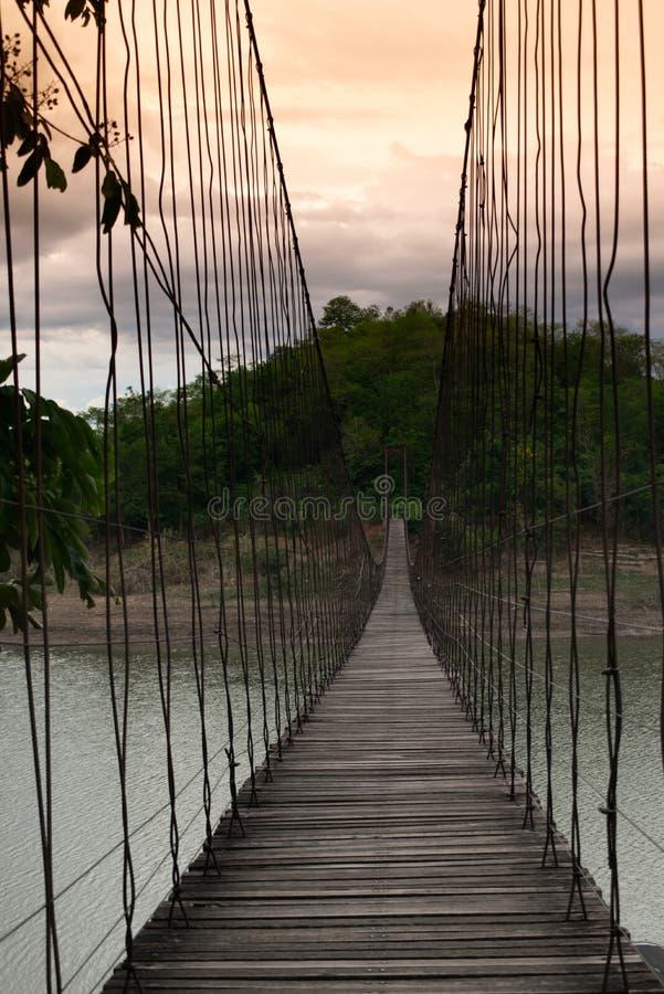 在绿色水湖的吊桥 免版税库存图片
