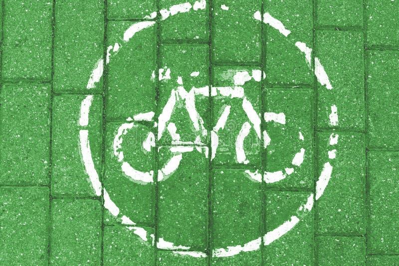 在绿色砖背景的白色自行车象,被定调子 免版税库存图片