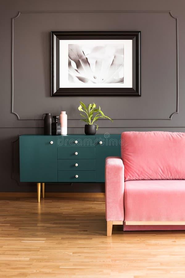 在绿色碗柜上的海报与桃红色长沙发的灰色顶楼内部的在木地板上 免版税库存图片