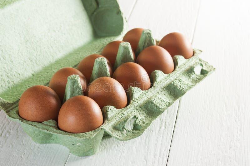 在绿色纸盒包裹的十个大棕色鸡鸡蛋在白色木桌上 库存照片