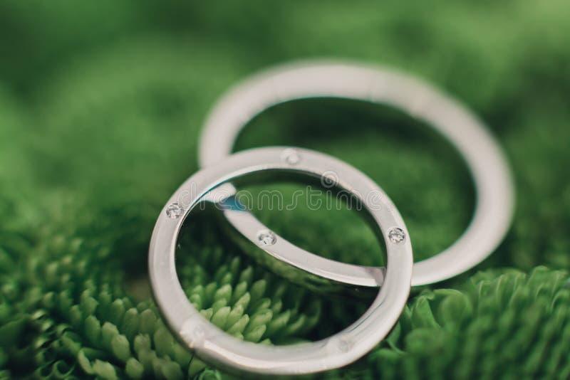 在绿色纹理的婚戒 免版税库存图片