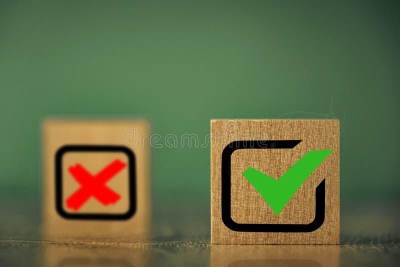 在绿色背景上具有复选标记图像的木立方体 库存照片