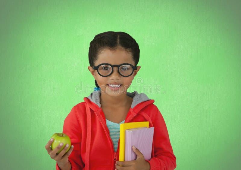 在绿色背景前面的女孩用苹果和书 免版税库存照片