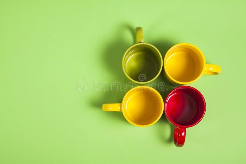在绿色背景的五颜六色的茶或咖啡杯 免版税库存图片