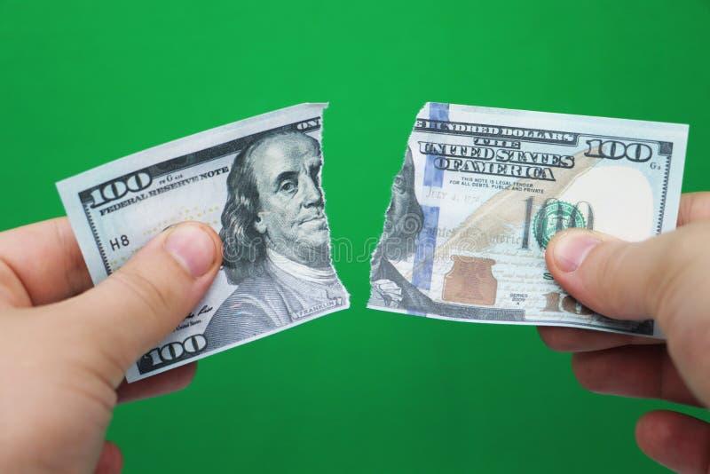 在绿色背景的人撕毁的美元 免版税库存照片