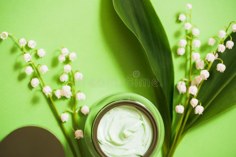 在绿色背景的化妆奶油和铃兰花 图库摄影