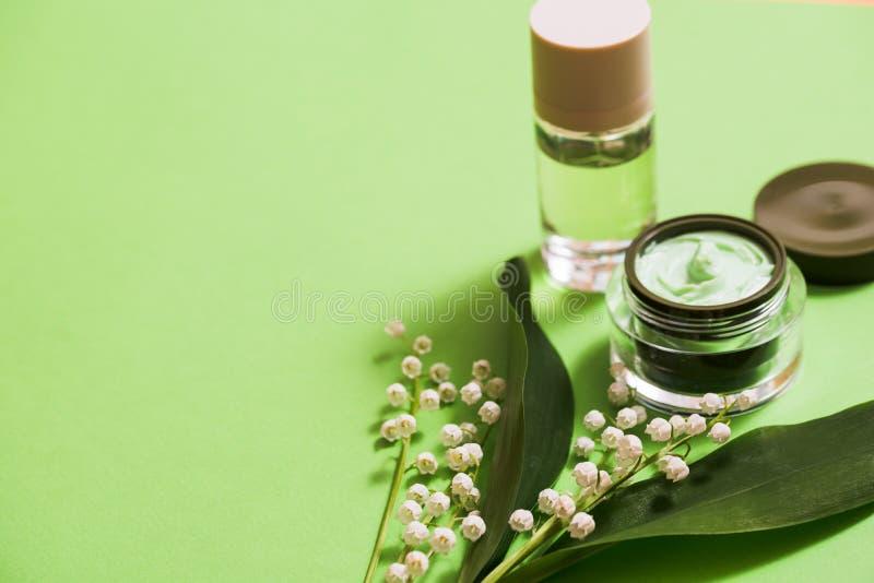 在绿色背景的化妆奶油和铃兰花 库存图片