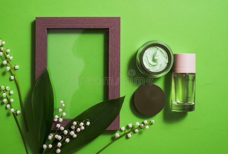 在绿色背景的化妆奶油和铃兰花 免版税库存照片