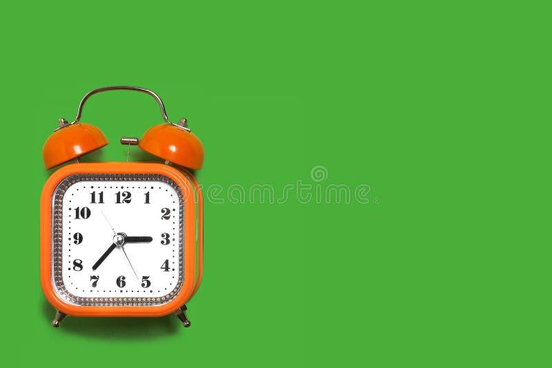 在绿色背景的橙色闹钟 库存图片