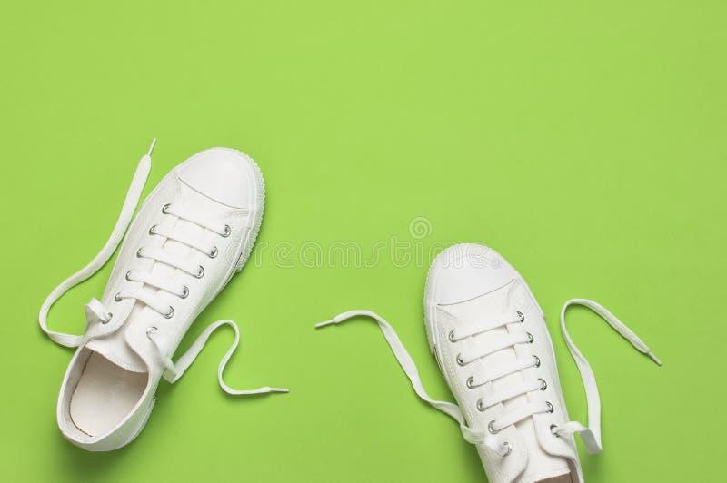 在绿色背景的白色女性时尚运动鞋 o 妇女的鞋子 时髦的白色运动鞋 ?? 库存照片