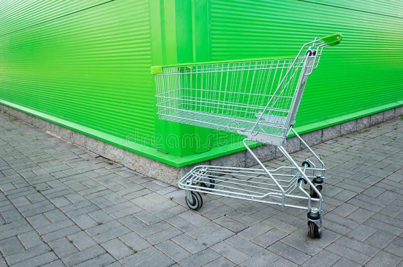 在绿色背景的空的购物车停车处与copyspace 外籍遭遇零售店 免版税库存图片
