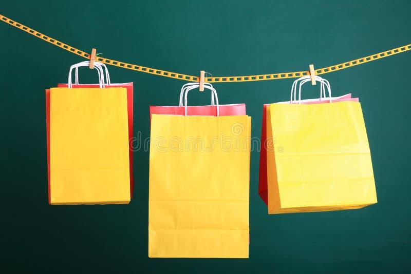 在绿色背景的购物的黄色礼品袋子 免版税库存图片