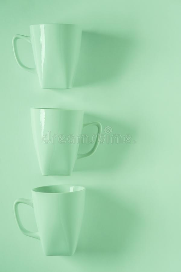 在绿色背景的3个绿色咖啡杯在与空的copyspace的垂直的行 库存照片