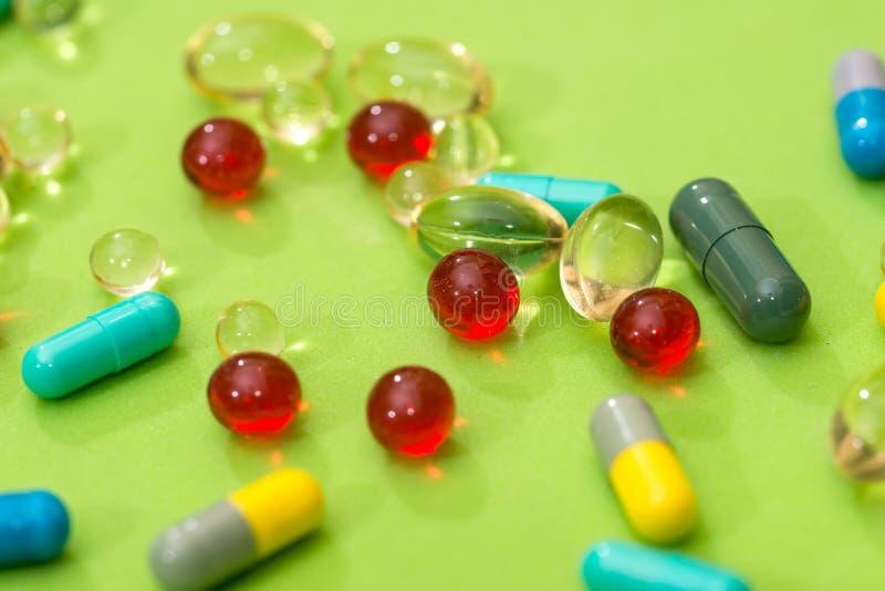 在绿色背景隔绝的许多不同的药片 库存照片