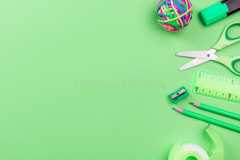 在绿色背景,平的位置的学校辅助部件,回到学校概念 库存图片