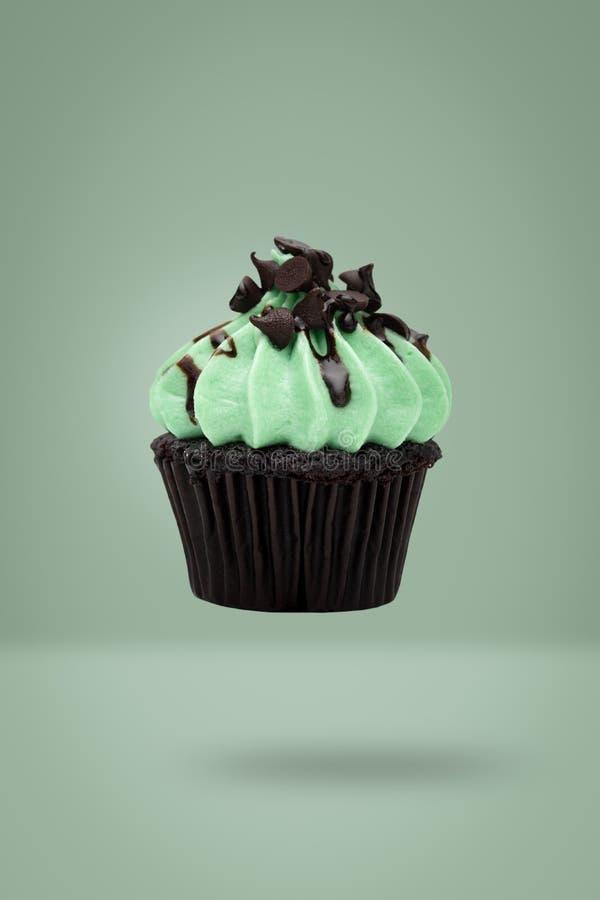 在绿色背景,想法最小的概念fo的薄荷的杯形蛋糕飞行 免版税图库摄影