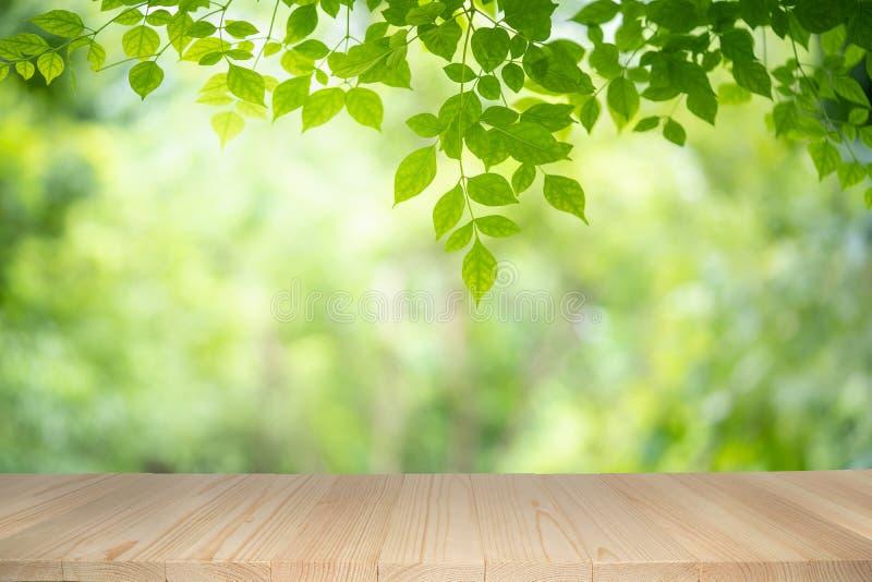 在绿色自然背景的空的木桌与在阳光下的秀丽bokeh 免版税库存照片