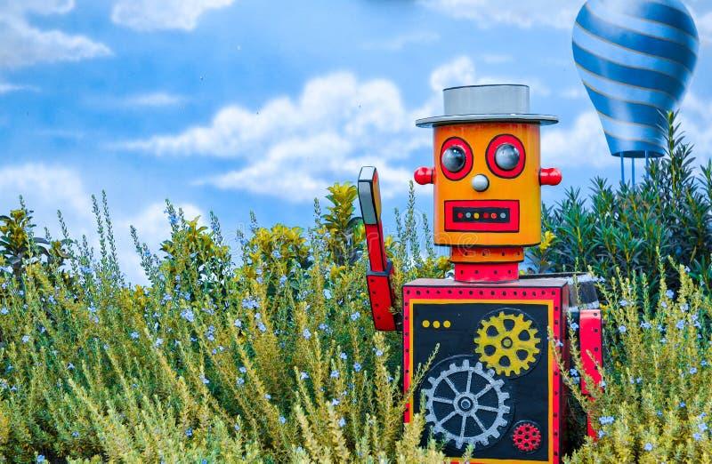 在绿色花卉背景的多彩多姿的明亮的木玩具机器人与后边蓝色轻快优雅和天空 图库摄影